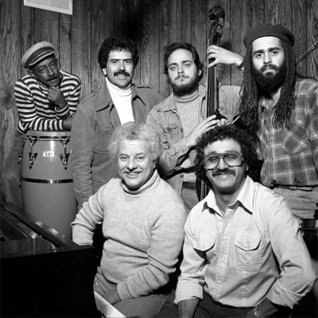 "Latin Percussion Ensemble Project: Carlos ""Patato"" Valdes, Johnny ""Dandy"" Rodríguez, Andy Gonzalez, and Alfredo de la Fé. Seated: Tito Puente and Edy Martínez. Photo by Martin Cohen."